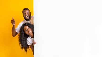 African couple posing with white empty board