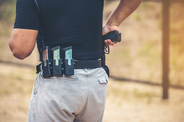The gun magazine at the man's waist is ready to be used with his sparkling pistol.