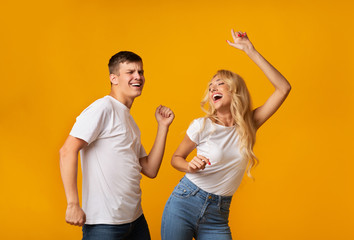 Emotional young couple dancing and laughing on yellow studio background