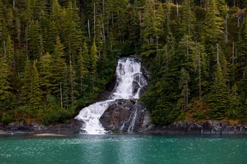 Beautiful flowing waterfall into the ocean in Endicott Arm fjord near Juneau Alaska