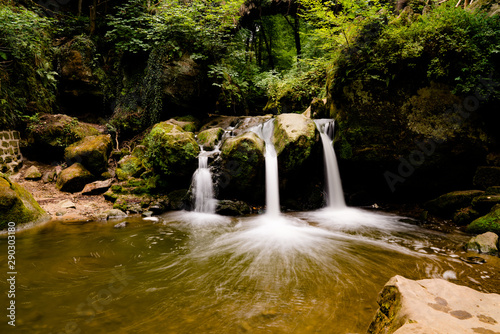 Wall mural idyllic small waterfall in lush green forest landscape