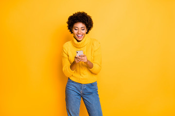 Yes I got new amount of likes. Photo of cheerful excited glad teen age girl using cellular in hand texting post commenting reposts wearing denim jeans pants isolated bright color background