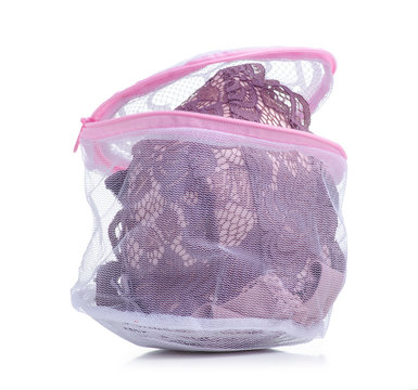 Pink laundry bag for underwear in hand on white background isolation
