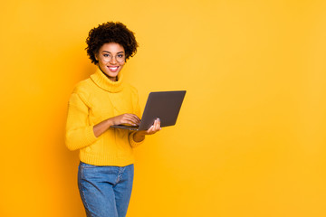 Copyspace photo of attractive intelligent cheerful business black stylish beautiful woman holding lap top with hands browsing through wearing yellow pullover isolated vivid color background