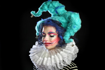 girl in makeup and costume jester . clown girl with bright makeup in blue wig On black background. eyes closed .