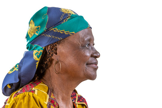 Portrait of African senior citizen woman in her 70- with a happy face in gold and brown dress