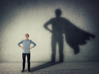 Casual teenage, keeps arms on hips smiling confident, casting a superhero with cape shadow on the wall. Student ambition success concept. Leadership hero power, motivation and inner strength symbol.