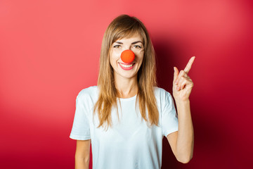 Young beautiful woman with a red nose of a clown on a pink background. Concept red nose day, holiday, party, clown