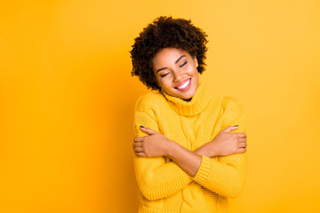 Photo of dark skin lady with closed eyes holding hands on shoulders wear warm knitted jumper isolated yellow background