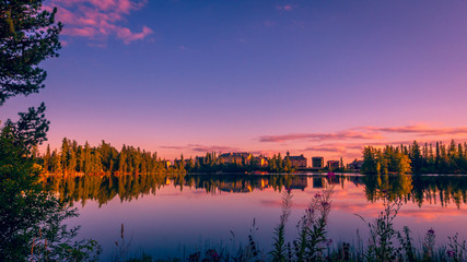 Sunset over Strbske pleso - tarn in High Tatras national park, Slovakia. There are trees and chalet reflections in the lake
