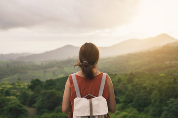 Young woman traveler looking at sunset over the mountain