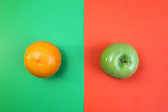 fruits orange and green apple lie on the halves of multi-colored paper