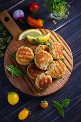 Fish cakes with lemon and herbs. Fish patties on wooden board. Overhead, vertical image