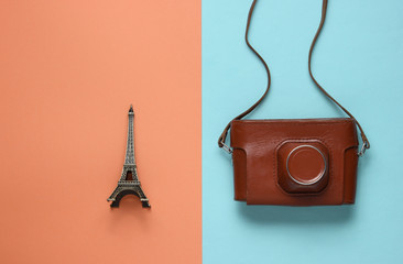 Retro picture with retro camera and eiffel tower figure on colored paper background.