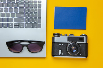 Summer leisure. Summertime relax.Laptop and travel accessories on yellow background. Studio short. Beach object. Top view. Flat lay