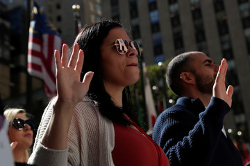 Citizenship candidates raise their hands during the Pledge of Allegiance at the U.S. Citizenship and Immigration Services (USCIS) naturalization ceremony at Rockefeller Plaza in New York City