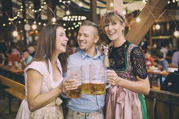 Fototapete - Gruppe von Volksfest Besuchern auf dem Oktoberfest