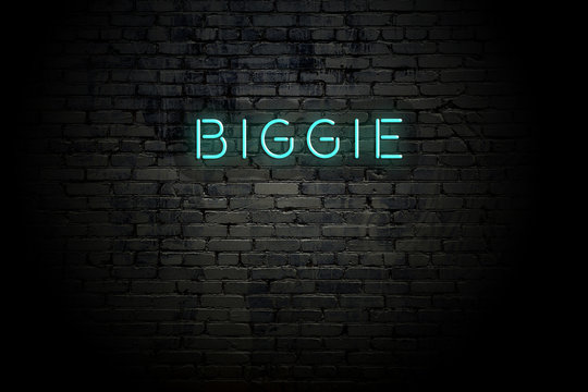 Highlighted brick wall with neon inscription biggie