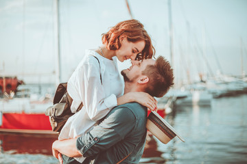 Romantic concept. Young couple in love at sea on a background of yachts club. Youth Lovestory