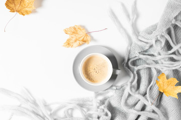 Fall cozy composition. Cup of coffee, yellow dry leaves and warm knitted gray plaid. Winter concept. Autumn background. Flat lay, top view, copy space