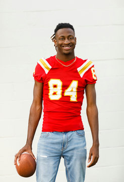happy smiling young Handsome African American Black Male outside wearing a red and gold football jersey and holding a football. he is wearing jeans and he is a high school student-athlete