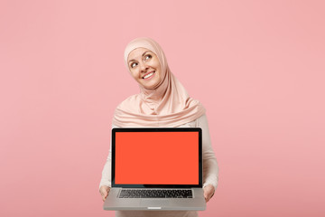 Pensive arabian muslim woman in hijab light clothes posing isolated on pink background. People religious Islam lifestyle concept. Mock up copy space. Hold laptop pc computer with blank empty screen.