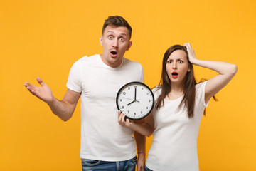 Perplexed young couple two friends guy girl in white empty blank design t-shirts posing isolated on yellow orange wall background. People lifestyle concept. Mock up copy space. Holding in hands clock. Fototapete