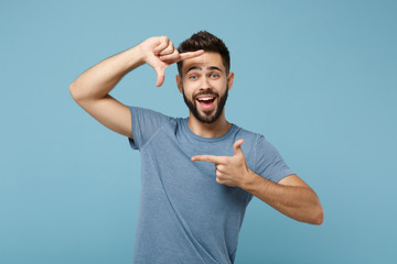Young cheerful funny man in casual clothes posing isolated on blue wall background, studio portrait. People sincere emotions lifestyle concept. Mock up copy space. Making hands photo frame gesture.
