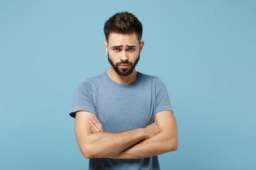Young dissatisfied offended man in casual clothes posing isolated on blue background, studio portrait. People sincere emotions lifestyle concept. Mock up copy space. Standing, holding hands crossed.