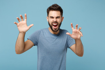 Young crazy man in casual clothes posing isolated on blue background in studio. People sincere emotions lifestyle concept. Mock up copy space. Shouting, growling like animal, making cat claws gesture.