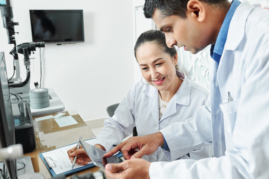 Indian male doctor pointing at digital tablet and talking to his Asian colleague while they working in team at the table at office