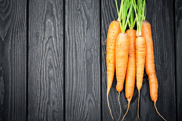 Carrots with halm on wooden background