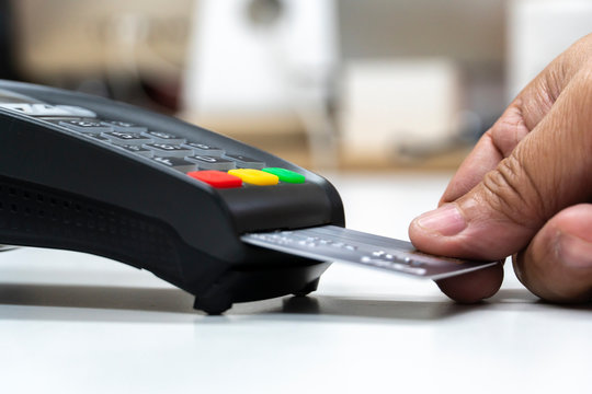 man hand with credit card swipe through terminal for payment, buy and sell products