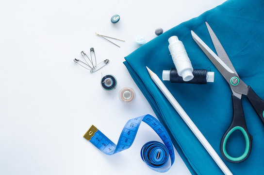 Desktop Accessories for sewing on a white background. Roll of blue satin fabric, tape measure, scissors, needles. Fashion, Design studio for tailoring, atelier concept.  Flat lay, top view, copy space