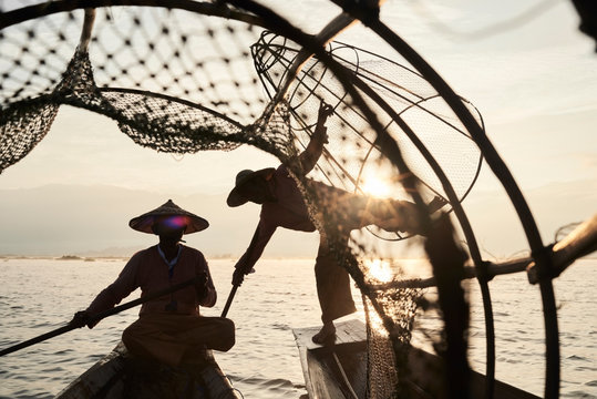 Traditional Shan fishermen at sunrise in boat on lake.