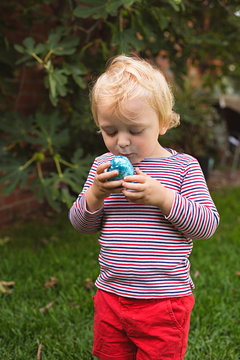 A young toddler boy has a chocolate easter egg hunt in his backyard in Australia