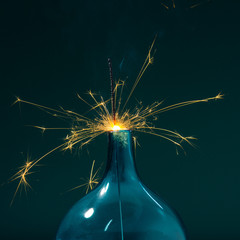 Sparkler burning down into a teal vase with space for copy