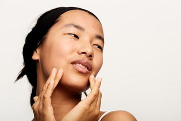 Young natural asian woman portrait applying moisturiser.