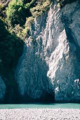 Glacial water runs alongside a steep white cliff.