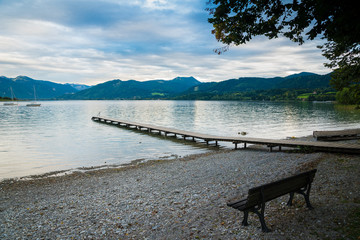 Wooden pier and bench in the beach of Tegernsee lake near Gmund am Tegernsee in Germany