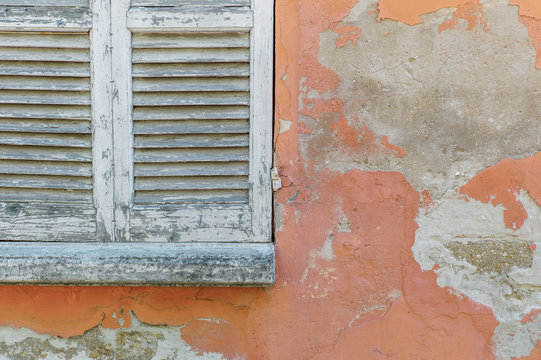 Window shutters in weathered house wall