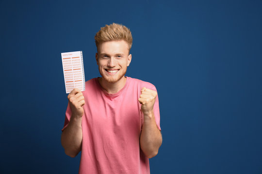 Portrait of happy young man with lottery ticket on blue background