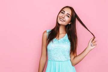 young girl, in a bright dress, smiling and posing on a pink background