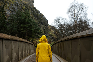 woman wearing a yellow raincoat in the middle of a bridge
