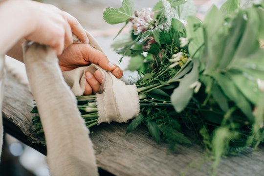 Crop florist tying up bouquet