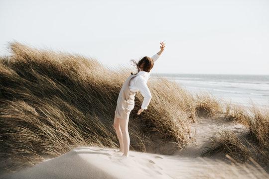 Teenage girl dancing on sand dune