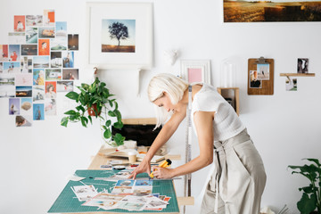 Young woman cutting photos for collage