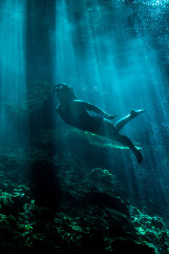 A young women swimming underwater in a cenote in Mexico with sunlight beams shining through.