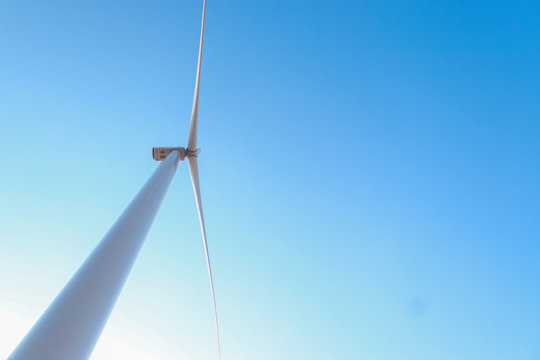 Looking upward to a big wind turbine and a blue sky. Alternative energy source, production and power generation. Ecology and freedom concept