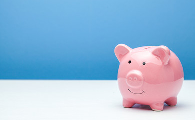 Pink piggy bank on a blue background. Copy space for text.
